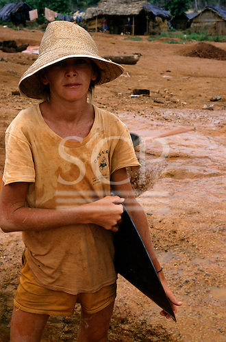 Ouro Verde mine, Para State, Brazil.  young goldminer looking serious, holding pan used for panning.