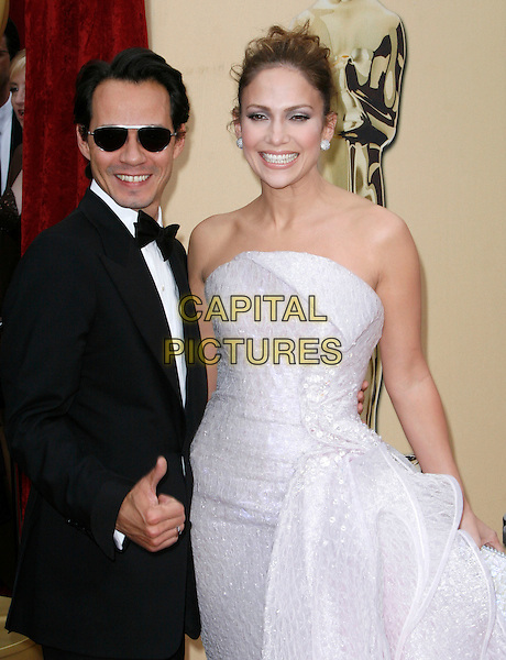 MARC ANTHONY & JENNIFER LOPEZ.The 82nd Annual Academy Awards held aat The Kodak Theatre in Hollywood, California, USA..March 7th, 2010 .oscars half length married husband wife sunglasses strapless dress cream sparkly nude beige off white hair up bun   Armani Prive silk satin black tuxedo tux bow tie shiny sunglasses shades smiling hand thumb up .CAP/EAST.©Eastman/Capital Pictures.
