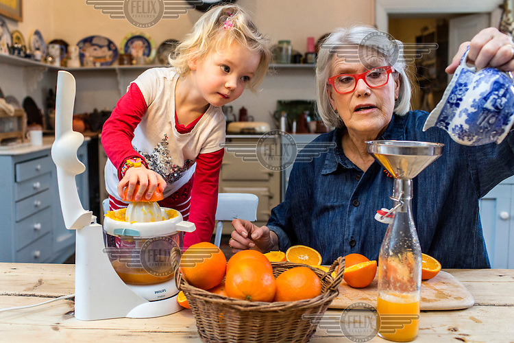 Irish chef and food writer Darina Allen prepares orange juice with her three year old grandchild, Ruby, at the Ballymaloe Cookery School.