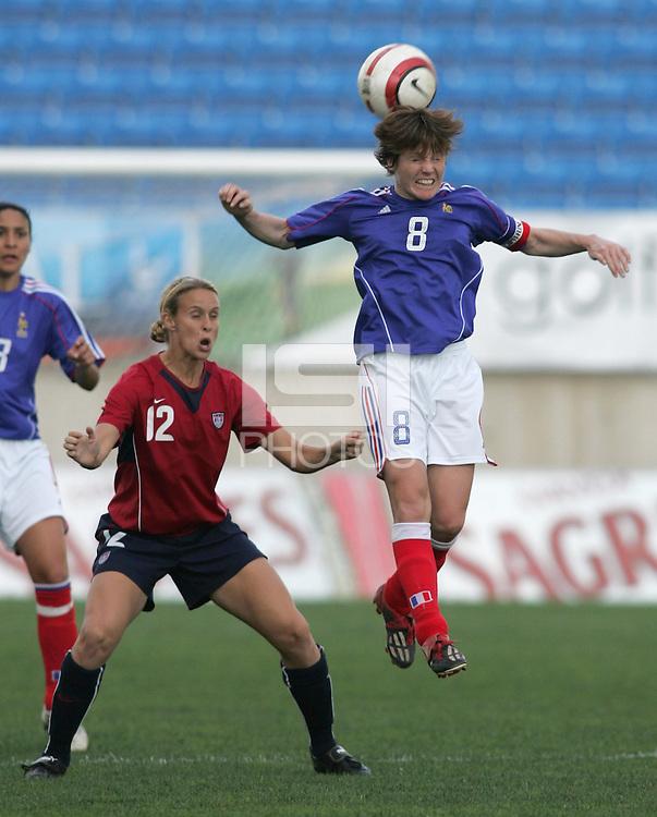 MAR 13, 2006: Faro, Portugal:  USWNT midfielder (12) Leslie Osborne stands behind the header of France midfielder (8) Sonia Bompastor in the Algarve Cup in Faro Portugal.