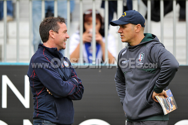 Bath Rugby Head Coach Mike Ford has a chat with London Irish Director of Rugby Brian Smith. Aviva Premiership match, between Bath Rugby and London Irish on September 28, 2013 at the Recreation Ground in Bath, England. Photo by: Patrick Khachfe / Onside Images