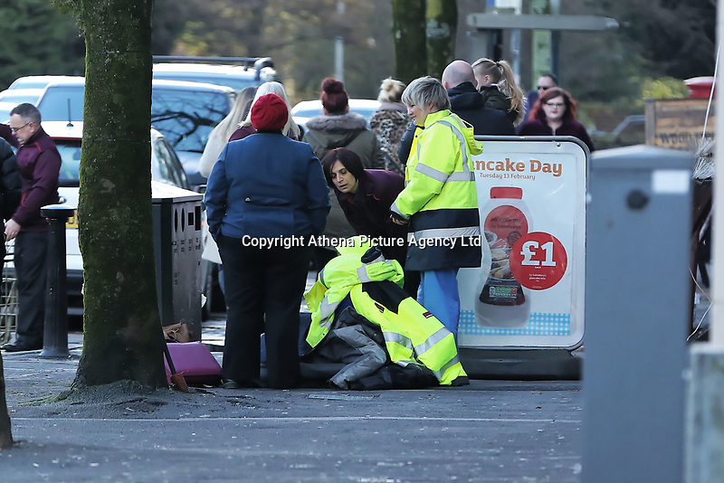 Pictured: A woman is given overcoats by store staff on the ground outside Sainsbury's in Swansea, Wales, UK.  Tuesday 13 February 2018<br /> Re: A Sainsbury's shop sign at the Uplands local store in the Uplands area of Swansea has collapsed onto the pavement hitting a woman in south Wales, UK.