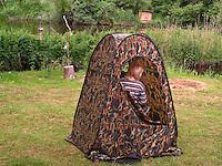 Kind sitzt in einem Tarnzelt und beobachtet Vögel