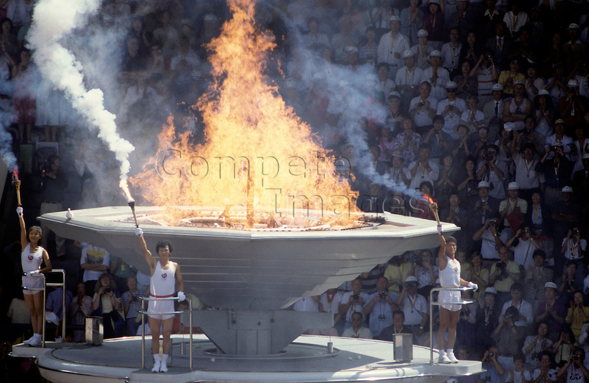 Olympic flame with crowd in background