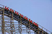Red roller coaster on tracks against blue sky