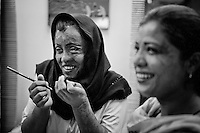 Saira Liaqat, 27 (L) shares a joke with her colleagues at a Depilex salon where she works as beautician in Lahore, Pakistan...Sara had acid thrown at her face 7 years ago by her husband while they where awaiting dowry from her family. Her husband had persistently asked Saira to move in with him, though the families had agreed that Saira should finish school first. Saira has undergone 9 sessions of plastic surgery. shares ajoke her friends and colleagues before the start of her shift at a Depilex salon in Lahore...Sara had acid thrown at her face 7 years ago by her husband while they where awaiting dowry from her family.
