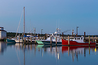 Commercial fishing boats docked in Menemsha Basin shortly before sunrise, in the fishing village of Menemsha in Chilmark, Massachusetts on Martha's Vineyard.