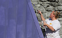 NWA Media/DAVID GOTTSCHALK - 12/15/14 -  Angela Watts, with CertaPro Painters, puts a layer of purple paint on the Slim Chickens restaurant on College Avenue in Fayetteville Monday December 15, 2014. Watts and her crew were using a cold weather paint that allows them to work in lower temperatures.