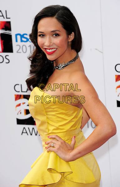 MYLEENE KLASS .Attending the Classical BRIT Awards at the Royal Albert Hall in London, England, UK, May 13th, 2010. .arrivals Brits half length strapless yellow dress hand on hip  smiling red lipstick make-up bird silver animal choker necklace side .CAP/CJ.©Chris Joseph/Capital Pictures.