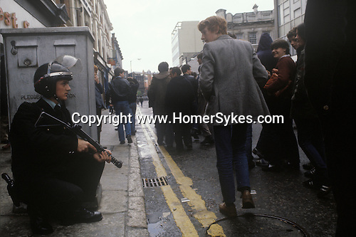 Northern Ireland The Troubles. 1980s. 1981 RUC policeman  with rifle that shoots rubber bullets polices are march through the centre of Belfast.