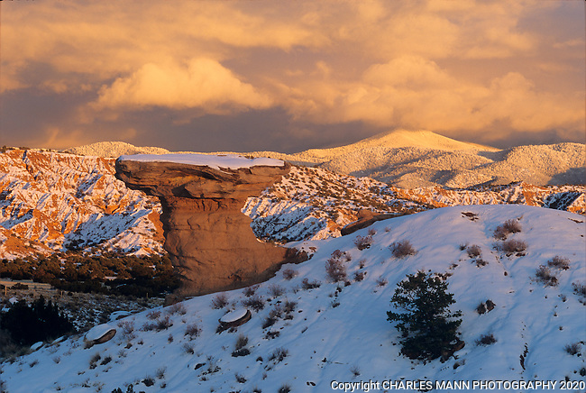 A snowfall on the Sangre de Cristo Mountains serves to emphasize the otherworldly quality of Camel Rock, a geologic formation at a roadside park on Tesuque Pueblo  just north of Santa Fe, New Mexico.