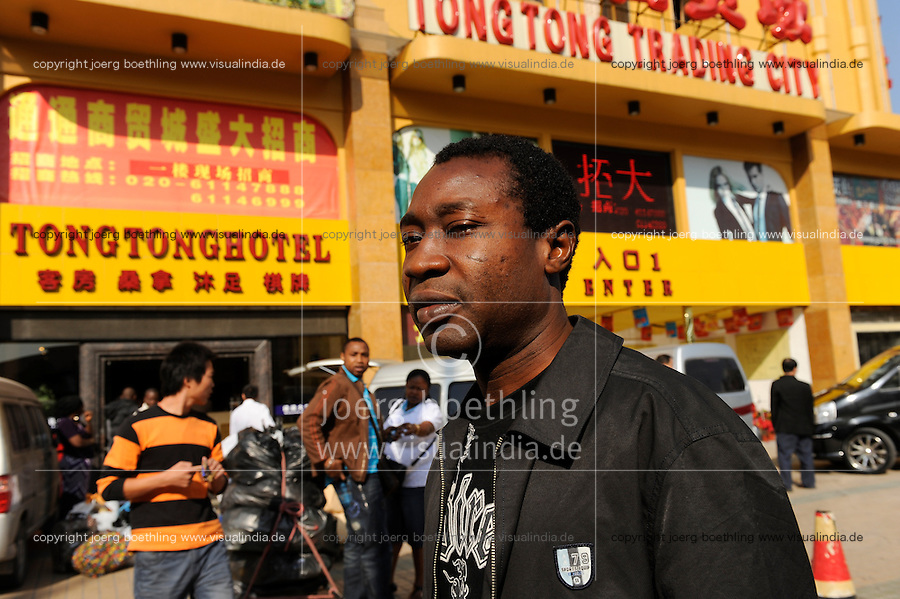 CHINA Guangzhou , african trader buy  textiles in export- and wholesale markets which the ship to Africa for their shops, Nigerian Ikechukwu Nwanzi in front of Tong Tong Hotel / CHINA , Provinz Guangdong , Metropole Guangzhou (Kanton) , Haendler aus Afrika kaufen in Grosshandels-/Exportmaerkten Textilien fuer Ihre Laeden in Afrika ein, Nigerianer Ikechukwu Nwanzi vor einem Textilmarkt und Tong Tong Hotel