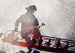 East Hartford firefighter Jeff Graham is inadvertently caught in a burst of water as the stream of water is turned on prematurely on the ladder truck,  as firefighters from East Hartford and assisted at the scene by Manchester Fire Rescue and EMS battle a two-alarm fire on a used appliance store on Tolland Street early Wednesday morning, April 11, 2018, in East Hartford. (Jim Michaud / Journal Inquirer)