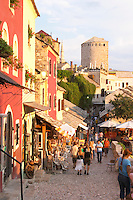 The busy old market bazaar street Kujundziluk with lots of tourist craft and art shops and street merchants. Sunset late afternoon light. Historic town of Mostar. Federation Bosne i Hercegovine. Bosnia Herzegovina, Europe.