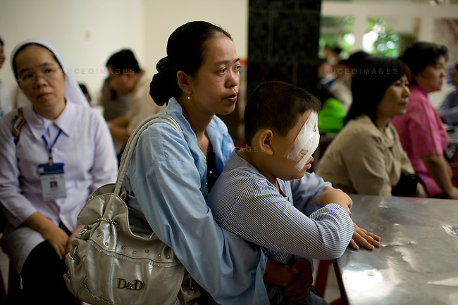 Binh Vo holds her son Hung Nguyen, 11, as they wait for Dr. James Brandt to examine him post surgery. Nguyen underwent surgery on his right eye to help reduce the amount of blindness due to glaucoma. Nurse Trinh Hoa looks on at left. Photo taken Wednesday, April 15, 2008.  Kevin German /  kevin@kevingerman.com..ORBIS Flying Eye Hospital brought doctors, nurses and specialists from all over the world to Ho Chi Minh City, Vietnam from April 7-18, 2008.  The ORBIS program contributed to the efforts of Ho Chi Minh City Eye Hospital in fighting avoidable blindness by educating local ophthalmologists to diagnose and manage pediatric blindness, retinal disease, oculoplastics, and blindness due to glaucoma..