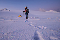 Female hiker stands near winter camp, Ytresandheia, Moskenesøy, Lofoten Islands, Norway