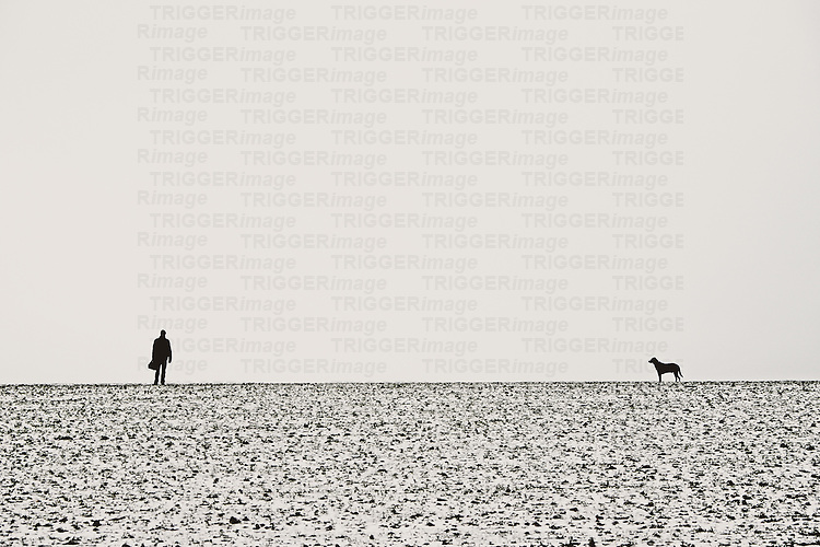 a man and a dog standing on a field of mus and snow