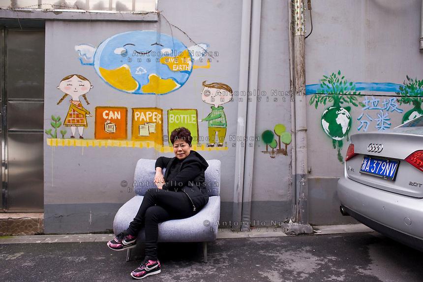 Una donna siede su un divano in una strada di un quartiere popolare di Hangzhou.<br /> A woman sitting in a sof&agrave; on the street.