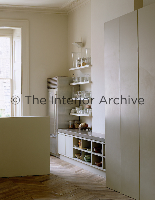 Open shelves store crockery and glassware and beneath the low-lying stainless steel work surface is further storage in this contemporary kitchen