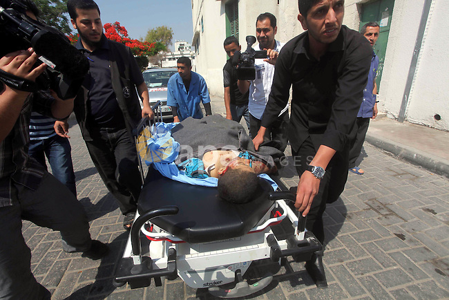 Palestinian men carry the body of Moamen al-Adam, 14, to the morgue of Al-Shifa hospital in Gaza City on June 20, 2012 after he was killed and his father Zohde Al-Dam in an Israeli air strike raising to eight the number of Palestinians killed in three days of violence, medics said. Adam died when a missile slammed into a farm in the Zeitun neighbourhood, east of Gaza City. Photo by Ashraf Amra