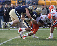 Pitt linebacker Max Gruder (55) and defensive back Jarred Holley (18) tackle Syracuse wide receiver Alec Lemon (15). The Pittsburgh Panthers beat the Syracuse Orange 33-20 at Heinz Field in Pittsburgh, Pennsylvania on December 3, 2011