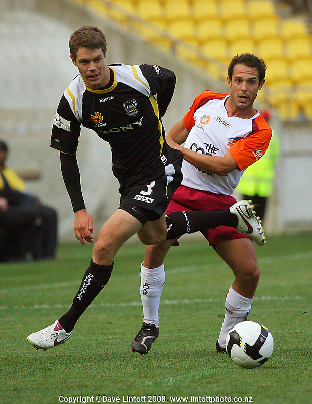 Tony Lochhead gets a pass away under pressure from Massimo Murdocca during the A-League football match between the Wellington Phoenix and Queensland Roar at Westpac Stadium, Wellington. Sunday, 26 October 2008. Photo: Dave Lintott / lintottphoto.co.nz