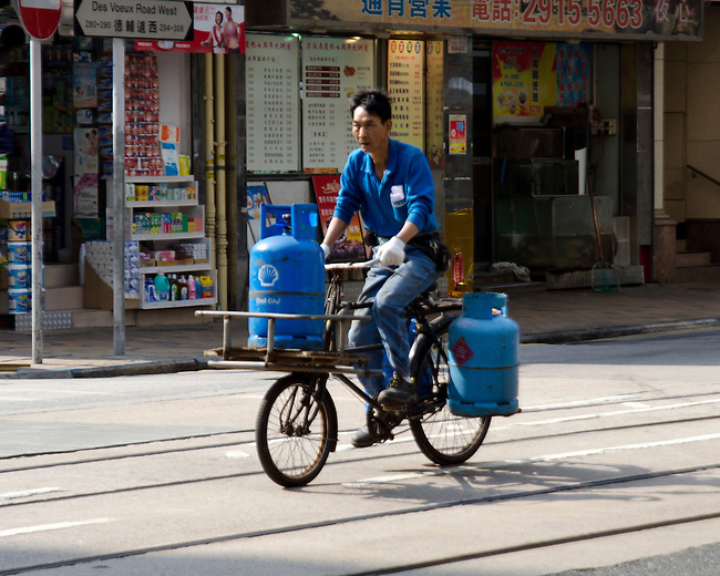 Hong Kong urban scene, delivery man on bicycle with gas cans.