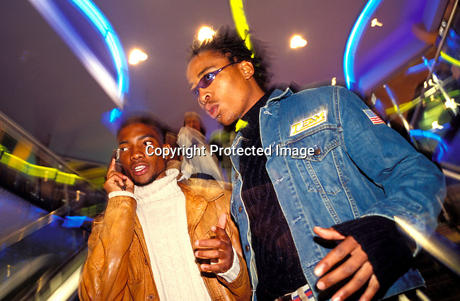 dippnig00068 Nightlife JOHANNESBURG, SOUTH AFRICA - MAY 28: Mzee Mbele, age 19, (left) a fashion student and his friend Marena Mosia, age 18, cruising in The Zone, a trendy shopping mall and gathering point for youth on May 28, 2002 in Rosebank a suburb in Johannesburg, South Africa.  Both live in black townships but come here on the weekends to hang out with other youth, black and white, to check out the latest fashion clubs etc, After eight years into democracy a new black middleclass and elite is growing, and they have money to spend on houses, cars and entertainment. .©Per-Anders Pettersson/iAfrika Photos...