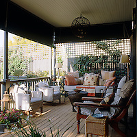 Green roller blinds provide protection from the sun on this terrace which is furnished with a wrought-iron daybed and a selection of armchairs in loose covers