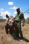 Orphan black rhino (Diceros bicornis),with security officer John Tanui at Lewa Wildlife Conservancy, Laikipia, Kenya, Africa, September 2012