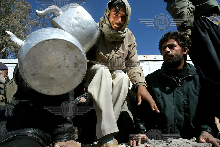 Aid workers distribute kettles and other goods to people displaced by the Bam earthquake..An earthquake measuring 6.3 on the Richter scale caused widespread devastation in the ancient city of Bam and other parts of Kerman Province, leaving at least 30,000 people dead.