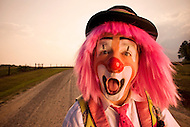 A clown gives a look of surprise while standing on an empty dirt road.