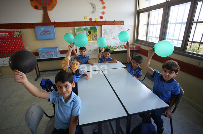 Palestinian schoolchildren play on the first day of a new school year, at a school in the West bank city of Nablus August 23, 2017. Photo by Ayman Ameen