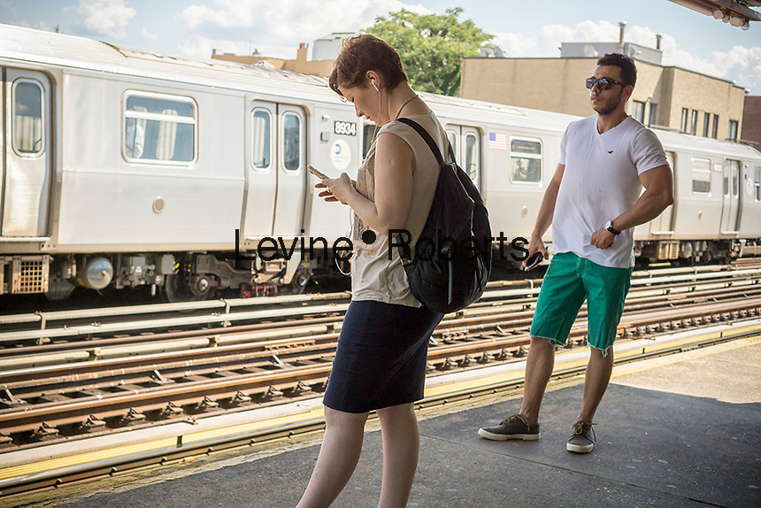 A woman preoccupied with her smartphone on a subway platform in New York on Sunday, August 7, 2016. (© Richard B. Levine)