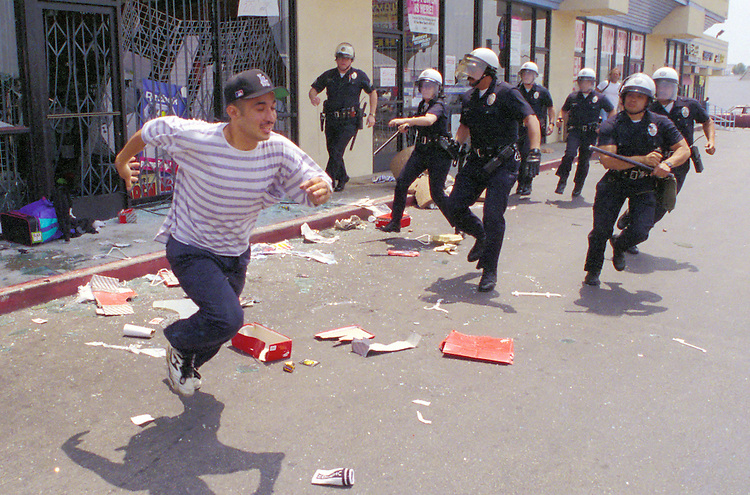 "A man runs from a sneaker shop eluding police who charged towards looters during the ""uprising"" of rioting and looting in the Koreatown neighborhood of Los Angeles, Calif. following the acquittal of LAPD officers accused of beating motorist Rodney King, May 30, 1992. Los Angeles suffered city wide chaos and destruction following the the end of the first trial against accused officers Sergeant Stacey Koon, Laurance Powell, Theodore Briseno and Timothy Wind. A later  Federal Civil Rights Trial sent officers Powell and Koon to prison for 30 months while Briseno and Wind were acquitted. Photo copyright Gerard Burkhart 818-207-0273)"