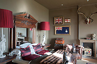 A pedimented wood-framed mirror serves as a headboard in this bedroom which is decorated with a traveller's memorabilia