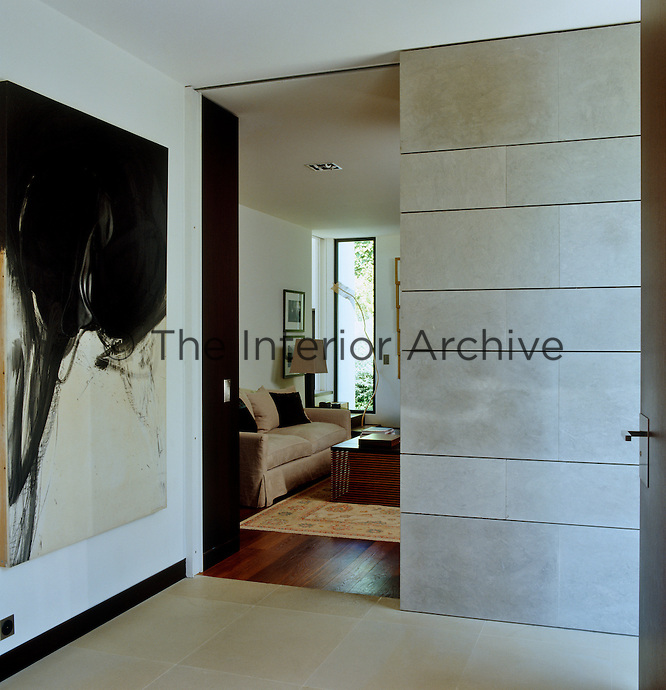 A large black and white abstract painting hangs on the wall of the landing and a sliding door in the concrete wall opens to the sitting room