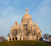 Sacré-Coeur Basilica, Paris, France, 1884-1914, Paul Abadie. A low angle view of the Basilica, showing the clustered white domes against against a clear sky on a winter morning. Built in white travertine on the top of the Butte de Montmartre, the Romano-Byzantine style Sacré-Coeur was designed as a monument to those who died in the Paris Commune during the Franco-Prussian War, 1870-71. Picture by Manuel Cohen