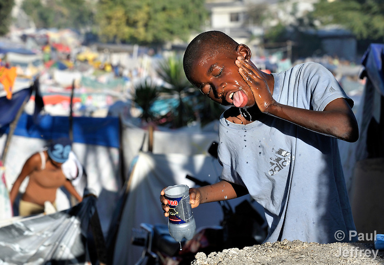A boy washes his face in a camp for homeless families set up on a golf course in Port-au-Prince, Haiti, which was ravaged by a January 12 earthquake.