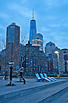 A view of Battery Park City and the new World Trade Center tower at sunset from the Hudson River Greenway pedestrain walkway; Hudson River and Battery Park City at sunset