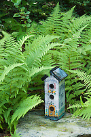 "Bird house with ferns, natural stone, shade garden, says ""Welcome"" on front and ""Feather Bed Inn"" on side, blue tall birdhouse"