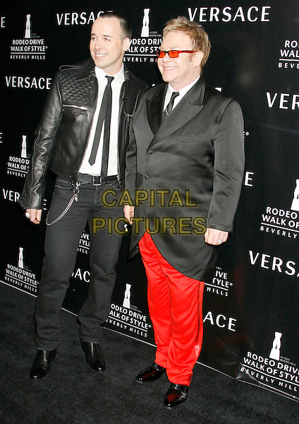 DAVID FURNISH & ELTON JOHN.Gianni And Donatella Versace Receive Rodeo Drive Walk Of Style Award held at the Beverly Hills City Hall, Beverly Hills, California, USA. .full length couple black suit jacket sunglasses shades red trousers leather.CAP/ADM/RE.©Russ Elliot/AdMedia/Capital Pictures