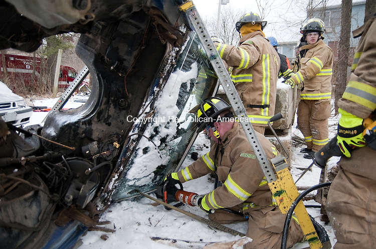 TORRINGTON, CT, 14 JAN 15 -  Torrington firefighter James Preuss uses the jaws of life to remove the roof of a Chevy Camaro during a training exercise Wednesday at Rick's Auto Parts in Torrington.   Alec Johnson/ Republican-American