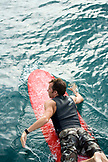 INDONESIA, Mentawai Islands, Kandui Resort, a man paddling to the surf on his longboard, Beng Beng surf break