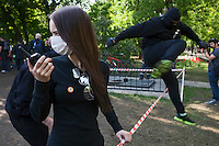 Moscow, Russia, 15/05/2012..A masked nationalist protester speaks on a walkie-talkie as another jumps a fence in Chistiye Prudy, or Clean Ponds, as a Moscow court ordered the eviction of some 200 opposition activists who have set up camp in the city centre park.