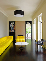 A bright yellow sofa in the living room is offset by a dark wooden floor