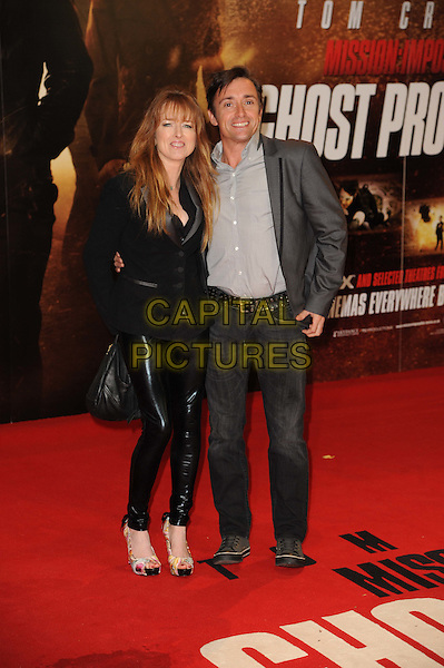 "Mindy & Richard Hammond.The ""Mission : Impossible Ghost Protocol"" UK premiere, BFI Imax cinema, Waterloo, London, England..December 13th, 2011.Mi4 MI:4 full length black leather pvc trousers top jacket grey gray shirt jeans denim married husband wife .CAP/CAS.©Bob Cass/Capital Pictures."