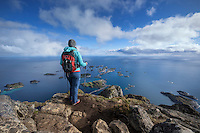 Female hiker with view over Henningsvær from summit of Festvågtind, Austvågøy, Lofoten Islands, Norway