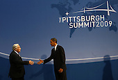 Pittsburgh, PA - September 24, 2009 -- United States President Barack Obama (R) shakes hands with Managing Director of the International Monetary Fund (IMF) Dominique Strauss-Kahn as they arrive to the welcoming dinner for G-20 leaders at the Phipps Conservatory on Thursday, September 24, 2009 in Pittsburgh, Pennsylvania. Heads of state from the world's leading economic powers arrived today for the two-day G-20 summit held at the David L. Lawrence Convention Center aimed at promoting economic growth.  .Credit: Win McNamee / Pool via CNP