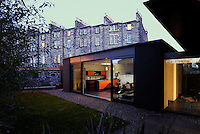 A view at night into the interior of a home that brings piece of Scandinavian Modernism to the heart of West Edinburgh. The owners took an opportunity to combine design ideas taken from rural Danish coastal dwellings and an urban British-Victorian aesthetic with the latest in eco technology. The house, juxtaposed with the surrounding period properties, definitely holds its own.